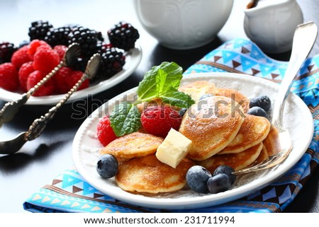 Dutch mini pancakes called poffertjes with berries, sprinkled with powdered sugar - stock photo