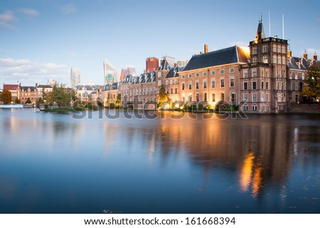 Dutch parliament buildings Binnenhof with skyscrapers in the background in Hague, Netherlands, during sunset - stock photo
