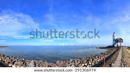 Dutch pastoral nature landscape with a small lighthouse on seacoast. Panoramic view (Marken. Netherlands) - stock photo