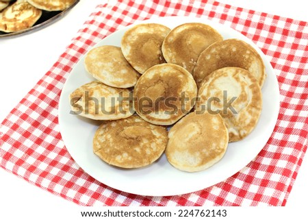 Dutch Poffertjes on a plate with napkin before light background