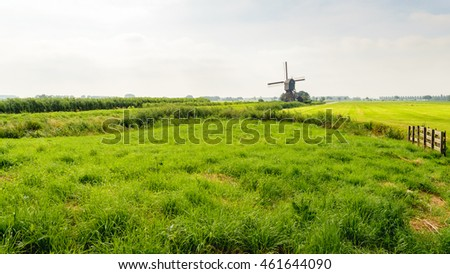 Dutch polder landscape in summer with some morning haze. The grass has different shades of green. In the background is a historic hollow post mill which regulated the water level in the polder.