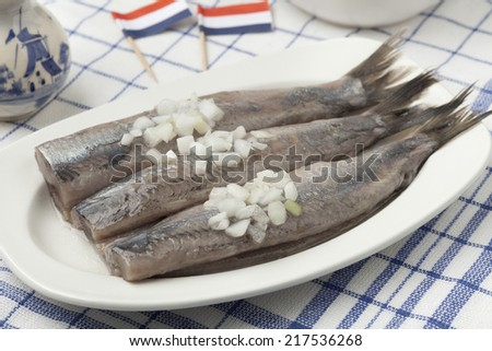 Dutch raw herring with onions on a dish - stock photo