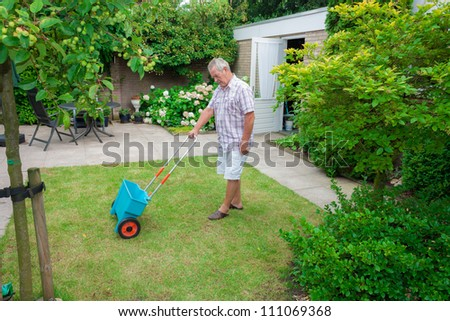 Dutch retired senior fertilising his grass lawn as retirement activity with a blue fertilizer dispenser on wheels - stock photo
