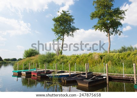 Dutch river in tranquil landscape with row boats - stock photo