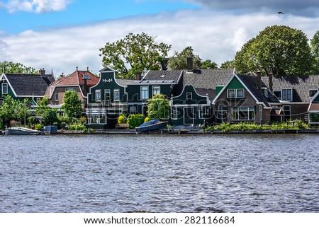 Dutch rural scenery: View of small Dutch village on the river shore near Zaanse Schans. The Netherlands. Zaanse Schans is a museum village in Zaandam with dutch houses and wind mills. - stock photo