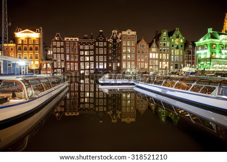 Dutch scenery with its canal side houses and tour boats - stock photo