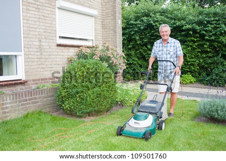 Dutch senior smiling and mowing his front yard grass with an electric mower as spare time activity after retirement - stock photo