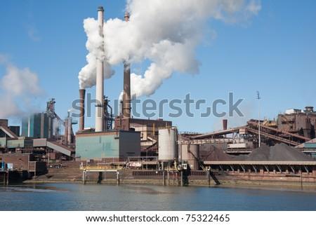 Dutch steel factory with big smokestacks - stock photo