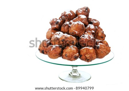 dutch traditional oliebollen with powder sugar on a glass-plate on white - stock photo
