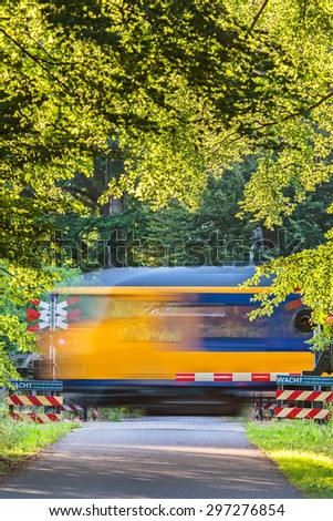 Dutch train passing a crossing in a forest in the province of Gelderland - stock photo