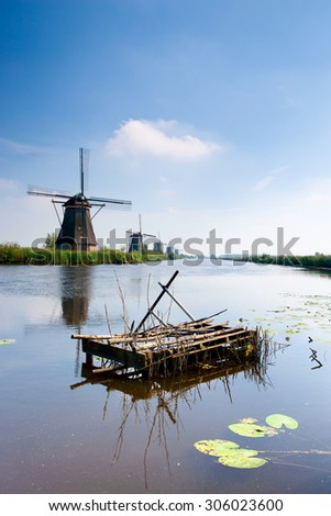 Dutch windmill and canal in Holland on a summer day with a blue sky and clouds in the background - stock photo
