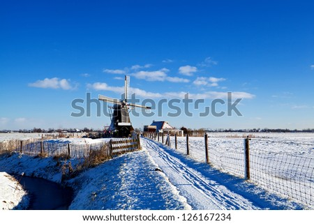 Dutch windmill and farmhouse in snow during winter - stock photo