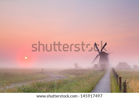 Dutch windmill and rising sun in fog, Groningen, Netherlands