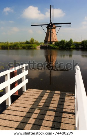 Dutch windmill at a river with a pier in the foreground