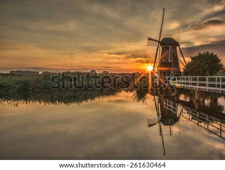 Dutch windmill at sunset - stock photo