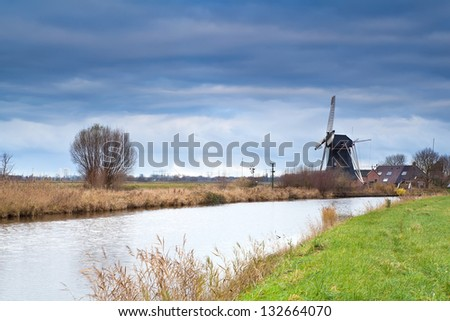 Dutch windmill by canal at clouded weather