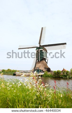 Dutch windmill in typical Hollands landscape near the river