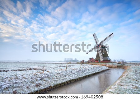 Dutch windmill in winter over blue sky, Holland - stock photo