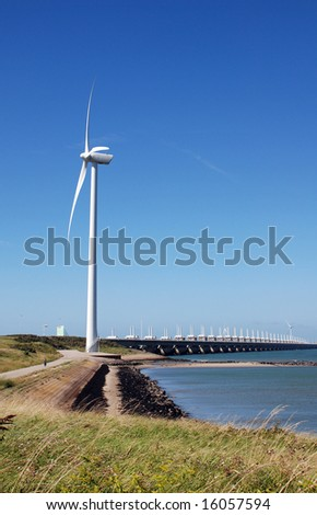 dutch windmill on dike and storm barrier oosterschelde - stock photo