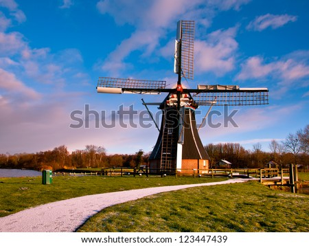 Dutch Windmill on the Waterfront of a Lake with Spectacular Clouds