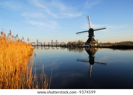 Dutch windmill reflection in water. - stock photo