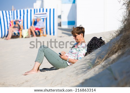 Dutch woman relaxing at the beach in Zeeland, Netherlands, on a bright summer day, looking at her smartphone and texting with her family - stock photo