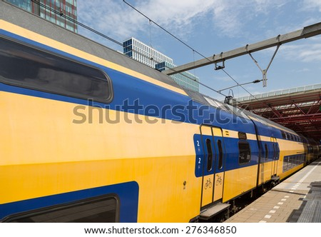 Dutch yellow double decker train is leaving a station - stock photo