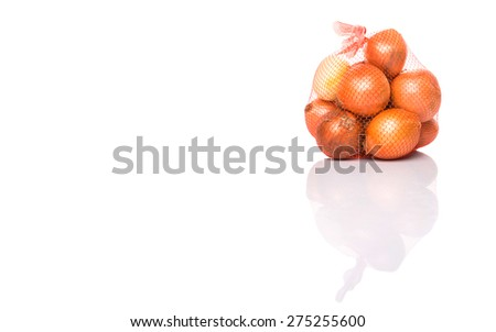 Dutch yellow onion in plastic sack over white background - stock photo