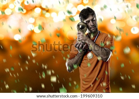 Dutchman soccer player, celebrating the championship with a trophy in his hand. On a orange lights background.
