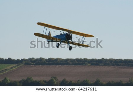 DUXFORD, UK - OCTOBER 10: Boeing Stearman biplane flies low during Autumn Air Show on October 10, 2010 in Duxford, UK