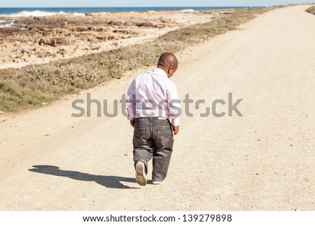 dwarfish african man walking down a dirt road along the coast with his head bent down