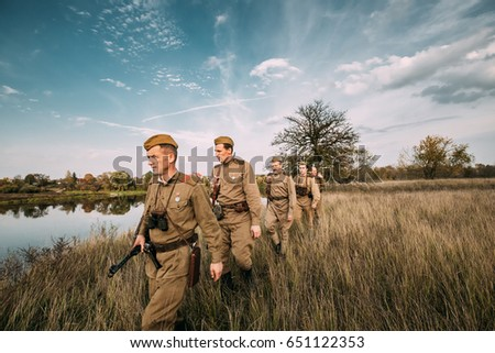 Dyatlovichi, Belarus - October 1, 2016: Group Of Reenactors Men Dressed As Russian Soviet Red Army Infantry Soldiers Of World War II Marching In Autumn Field With Weapons At Historical Reenactment