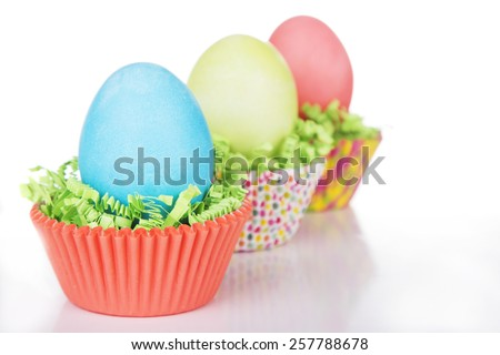Dyed Easter eggs in a nest of green grass confetti and cup cake wrappers - stock photo