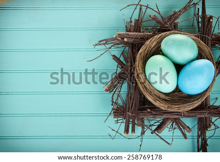 Dyed Easter eggs in a nest on a turquoise blue wood panel - stock photo