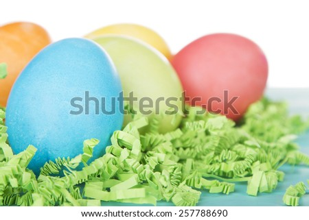 Dyed Easter eggs on green confetti grass - stock photo
