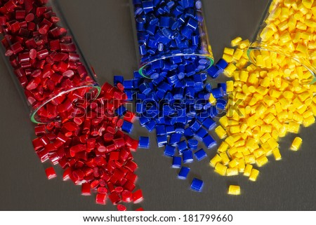 dyed polymer resin in test tubes on steel plate - stock photo