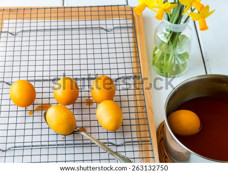 Dyeing Easter eggs natural way with turmeric for mustard - yellow color.  Selective focus. - stock photo
