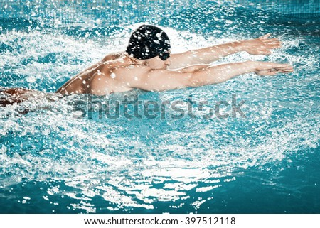 Dynamic and fit swimmer swims in a pool