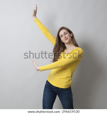 dynamic beautiful 20s woman wearing yellow sweater and jeans, showing something on her side with fun for copy space - stock photo