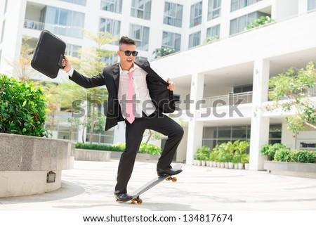 Dynamic businessman with positive attitude towards life balancing on a skateboard - stock photo