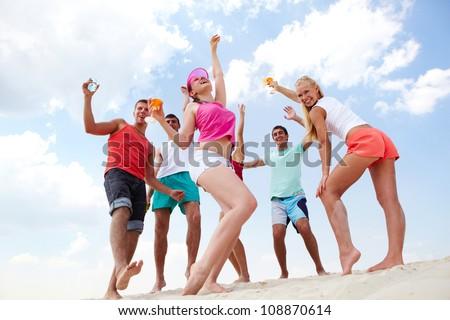 Dynamic friends having fun on the beach - stock photo