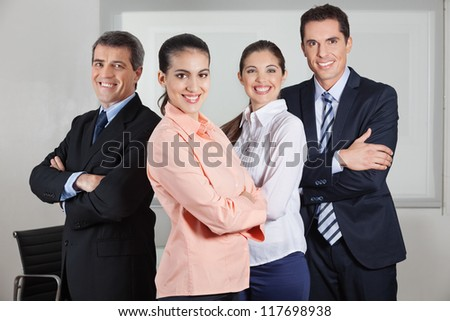Dynamic happy busines team standing in the office with the arms crossed - stock photo