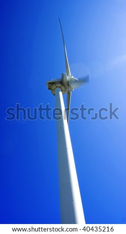 Dynamic image of a wind generator against blue sky, toward the sun with motion and lens flare