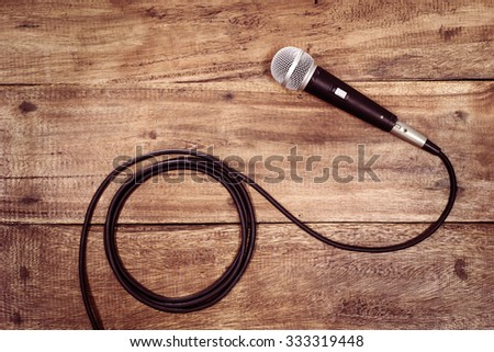 dynamic microphone on old wood for music background - stock photo