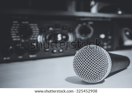 dynamic microphone & recording studio gears on background. black and white photo for studio music recording concept - stock photo