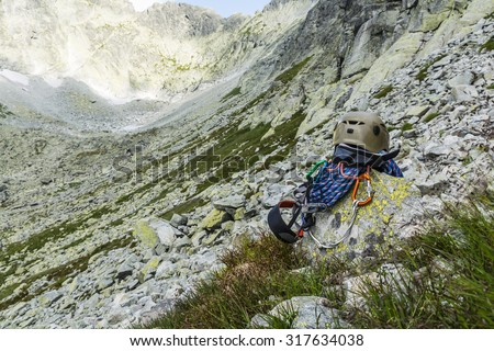 Dynamic rope, helmet, carabiners, climbing harness and descender on a rock ridge in the background