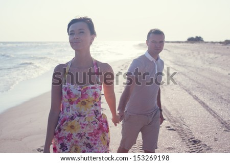Dynamic shot of happy smiling couple. Focus on guy. Walking on the beach. Holding each other and laughting - stock photo