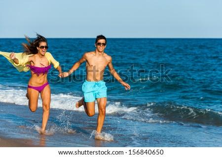 Dynamic teen couple running and splashing water at seaside.  - stock photo