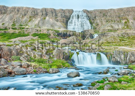 Dynjandi is the most famous waterfall of the West Fjords and one of the most beautiful waterfalls in the whole Iceland. It is actually the cascade of waterfalls. - stock photo