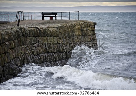DYSART, SCOTLAND - DECEMBER 25: waves crash into a pier on December 25, 2011 in Dysart, Scotland. Strong winds over the Christmas period caused havoc and power outages across central Scotland. - stock photo
